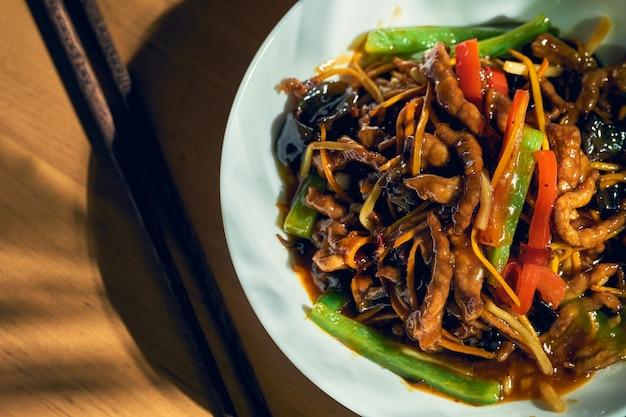 Maiale in agrodolce con verdure wok in una ciotola bianca. cucina cinese.