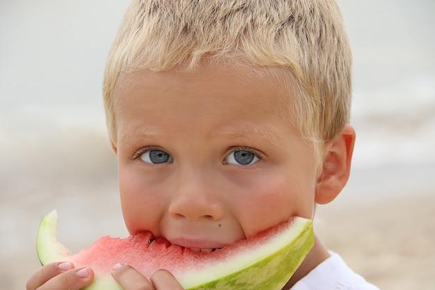 Dolce ragazzo biondo abbronzato sulla costa, che tiene in mano una fetta succosa di anguria e lo mangia. concetto estivo.