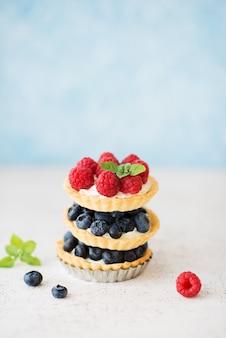 Crostate dolci con frutti di bosco freschi estivi, lamponi, fragole e mirtilli, fuoco selettivo