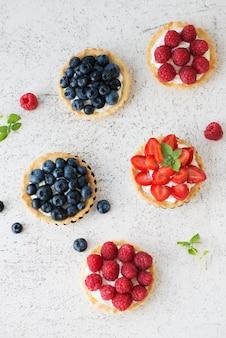 Crostate dolci con frutti di bosco freschi estivi, lamponi, fragole e mirtilli, vista dall'alto