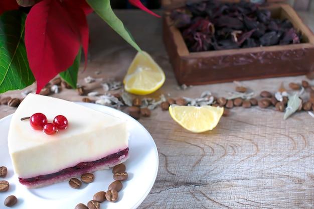 Dolce gustoso delizioso cheesecake con frutti di bosco su piatto bianco, scatola da tè, chicchi di caffè e limoni sul fondo della tavola in legno. cibo da dessert