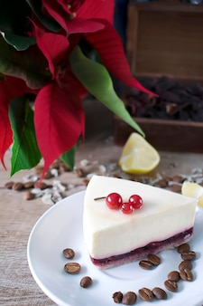 Dolce e deliziosa torta di formaggio con frutti di bosco su piatto bianco scatola da tè chicchi di caffè e limoni