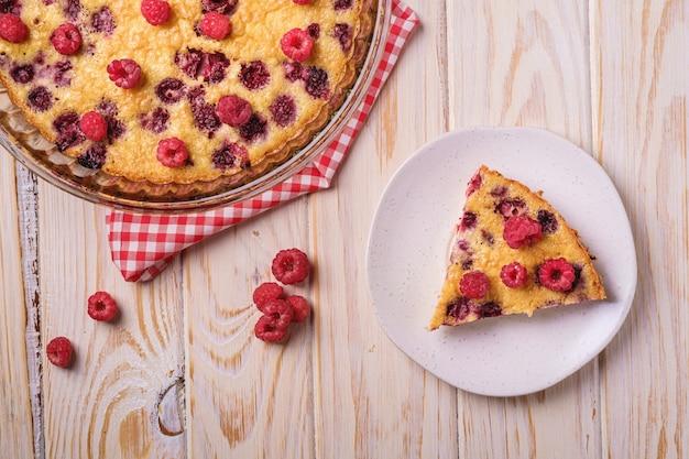 Torta dolce gustosa con frutti di lampone in gelatina e freschi in teglia e piatto con tovaglia rossa