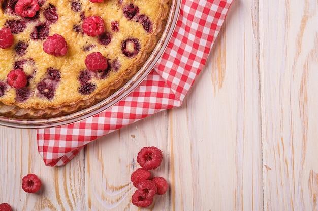 Torta dolce gustosa con frutti di lampone in gelatina e freschi in teglia con tovaglia rossa Foto Premium