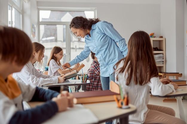 La dolce insegnante aiuta a leggere il suo studente. bambini delle scuole elementari seduti sulle scrivanie e leggere libri in classe.