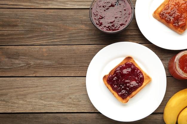 Toast dolci con marmellata e frutta per colazione su tavolo grigio, orizzontale