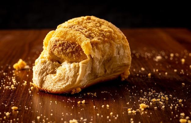 Pane crema alla vaniglia dolce e farina dolce, su un tavolo di legno marrone. è un tipo di pane comune in brasile e portogallo, fatto con pasta dolce.