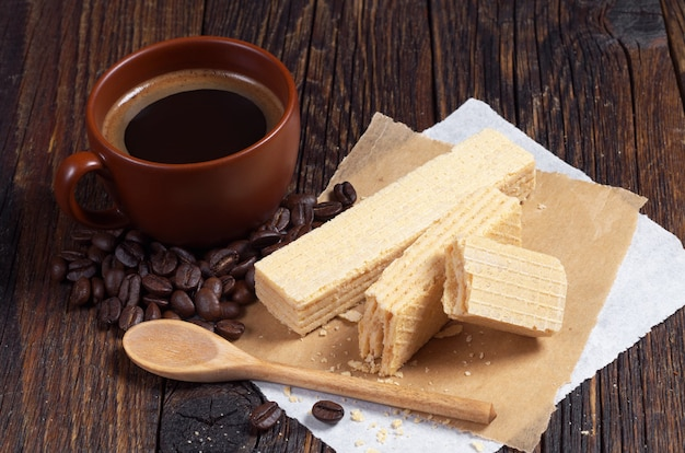 Cialde dolci e tazza di caffè caldo per colazione sul tavolo di legno scuro