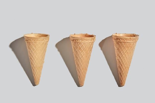 Coni di cialda dolce per dessert vuoto su uno sfondo di carta bianca con spazio di copia. concetto di cibo primaverile o estivo. vista dall'alto.