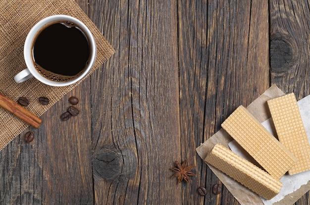 Cialde dolci e tazza di caffè caldo per colazione su tavola in legno rustico, spazio per il testo.