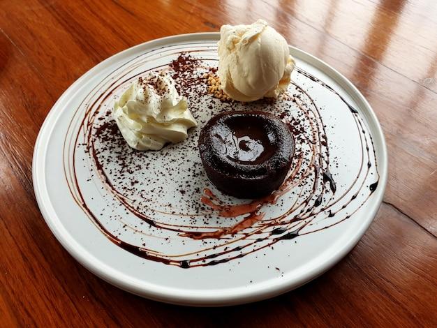 Torta di lava dolce al cioccolato caldo con gelato alla vaniglia e panna da montare su un piatto bianco