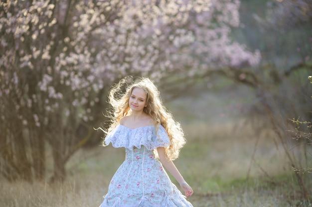 Dolce donna in un bel vestito, a piedi attraverso il parco con fiori nelle mani