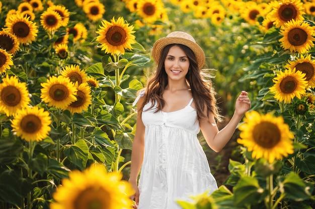 Donna dolce in un vestito bianco che cammina su un campo di girasoli