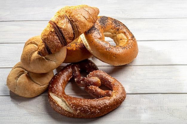 Prodotti da forno lievitati dolci. bagel, ciambelle, croissant, salatini. su uno sfondo chiaro. copia spazio.