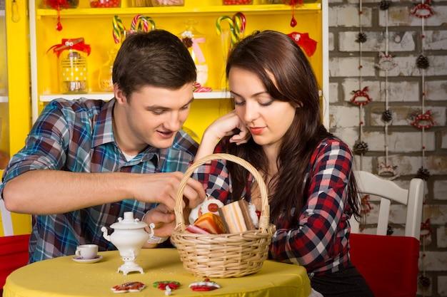 Dolci giovani amanti in camicie a scacchi incontri al negozio con cesto di pasticceria e bevande sul tavolo.