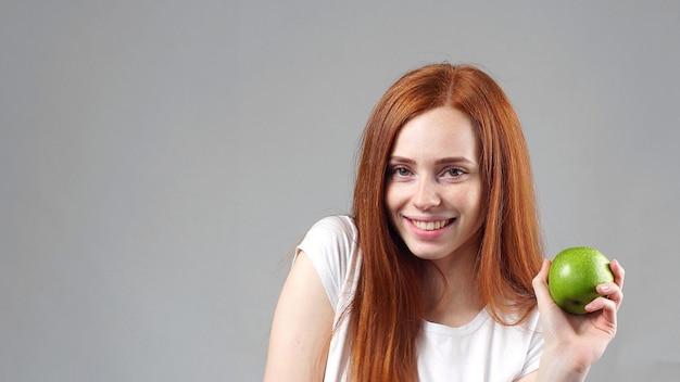Dolce giovane donna con una grande mela verde fresca che dà alla fotocamera un sorriso raggiante