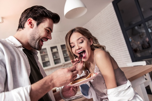 La colazione più dolce. uomo barbuto dai capelli scuri in una camicia bianca che sembra felice mentre dà da mangiare alla sua bella moglie
