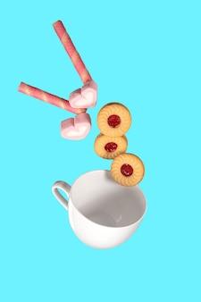 Dolci e biscotti in movimento volante da una tazza bianca. immagine di levitazione alimentare.