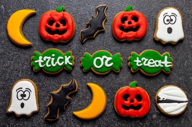Dolci pan di zenzero zucca di halloween fantasma zombie candy cane lettering dolcetto o scherzetto su uno sfondo di pietra scura