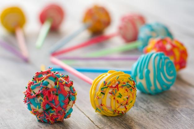 Dolci con glassa brillante. caramelle su superficie di legno grigia. cake pop dalla pasticceria. fai una piccola festa per i bambini.