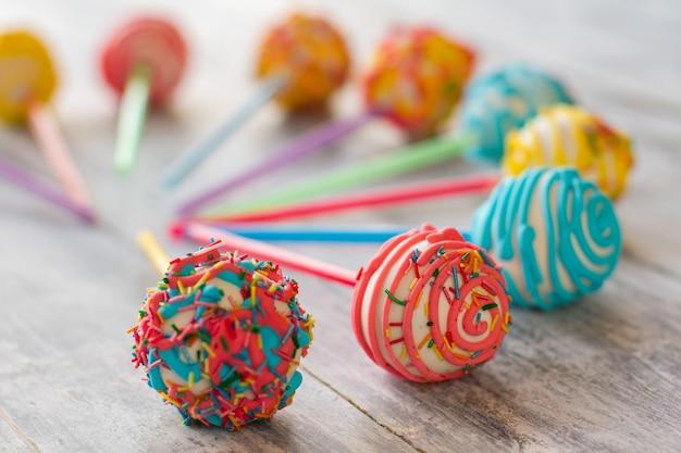Dolci con glassa. caramelle colorate su superficie in legno. cake pop per bambini. il gusto di una festa divertente.