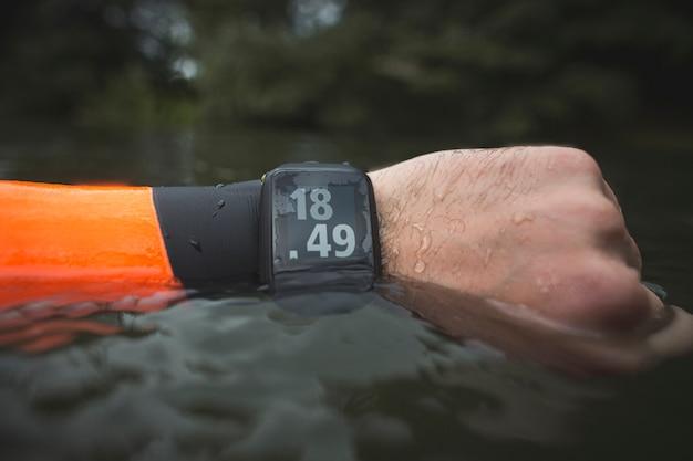 Braccio da nuotatore e mano chiusa con neoprene e orologio in acqua con foresta