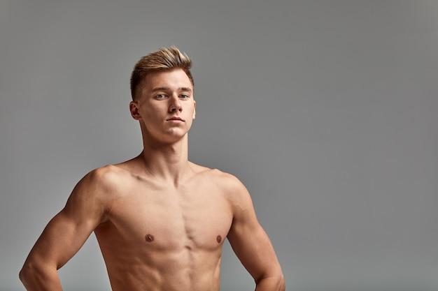 Nuotatore su sfondo grigio, mani sulla cintura, copia spazio, sfondo grigio, giovane nuotatore con un corpo perfetto.