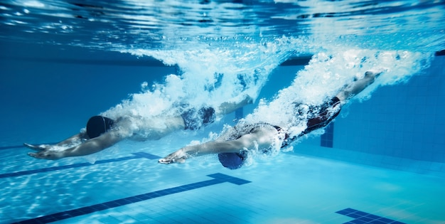 Nuotatore salto dalla piattaforma saltando una piscina. foto subacquea