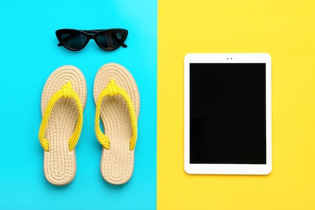 Accessori per il nuoto: occhiali neri alla moda, infradito estivo, tablet
