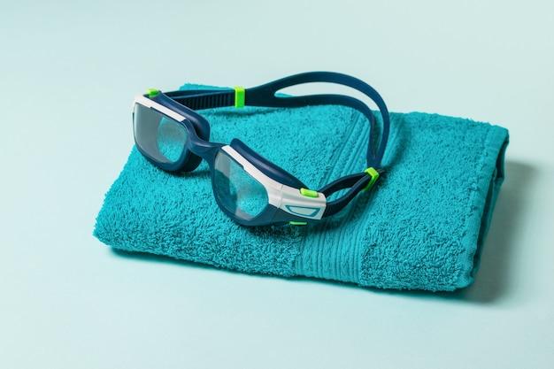 Occhiali da nuoto su un asciugamano blu. accessori per il nuoto in piscina.