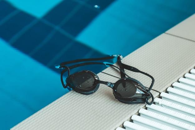 Gli occhialini da nuoto sono sul parapetto vicino alla piscina Foto Premium