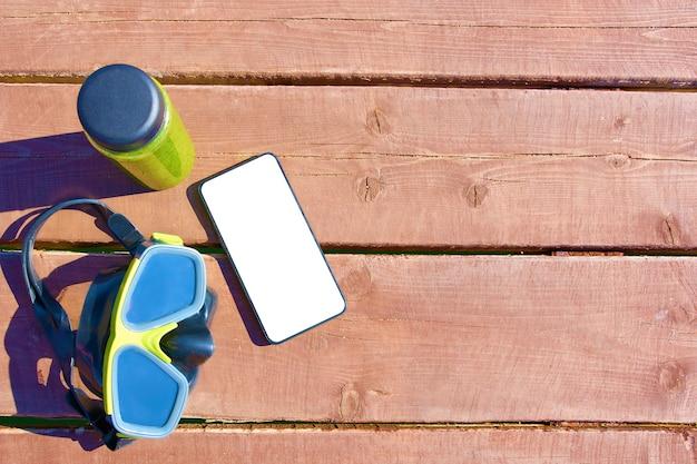 Maschera di nuoto, bottiglia di frullato e smartphone con schermo isolato sul tavolo di legno