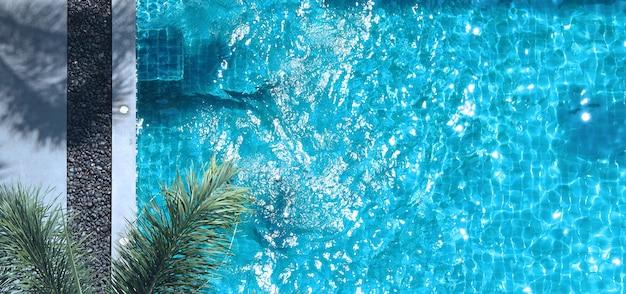 Acqua blu della piscina in estate e lettini da spiaggia bianchi e angolo di vista dall'alto.
