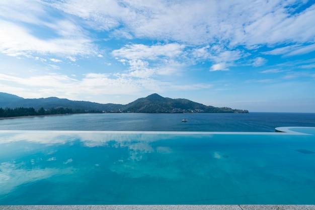 Piscina con scala in cima all'edificio sul tetto con vista sul mare tropicale, lussuosa villa sulla spiaggia con piscina vista mare dal design moderno, vacanze estive e concetto di sfondo di viaggio.