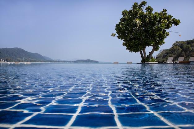 Piscina con un albero vicino alla spiaggia in giornata di sole. giorno di vacanza.