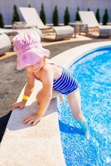 Nuoto, vacanze estive - ragazza sorridente adorabile in cappello rosa e costume da bagno blu che giocano in acqua blu in uno stagno.