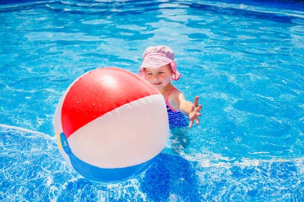 Nuoto, vacanze estive - bella ragazza sorridente in cappello rosa e costume da bagno blu che gioca in acqua blu con palla gonfiabile multicolore in una piscina