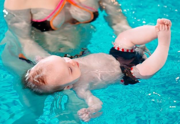 Un insegnante di nuoto insegna a un bambino a nuotare in piscina