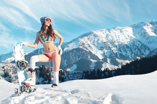 Lo snowboarder in costume da bagno incontra la primavera su un pendio in montagna.
