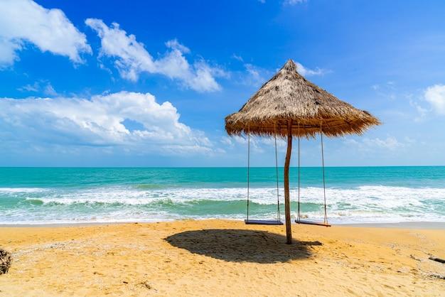 Altalena sulla spiaggia con mare oceano e cielo blu
