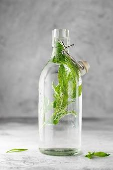 Bottiglia di vetro swing top con acqua fredda con foglie di menta fresca su cemento grigio.