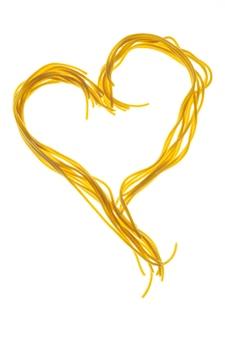 Riccioli di spaghetti cotti. spaghetti a forma di cuore.