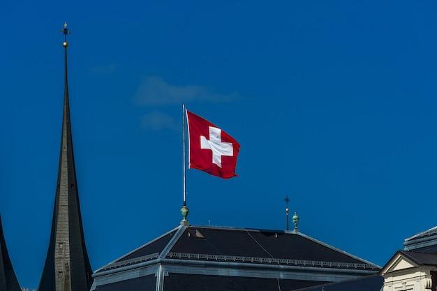 Bandiera svizzera che sventola nel vento contro un cielo blu