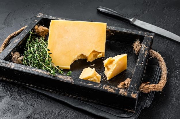 Pezzo di formaggio svizzero duro in vassoio di legno. sfondo nero. vista dall'alto.