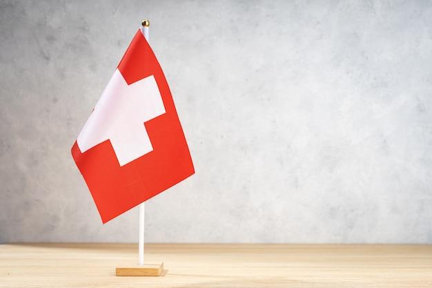 Bandiera da tavolo della svizzera sulla parete strutturata bianca. copia spazio per testo, disegni o disegni