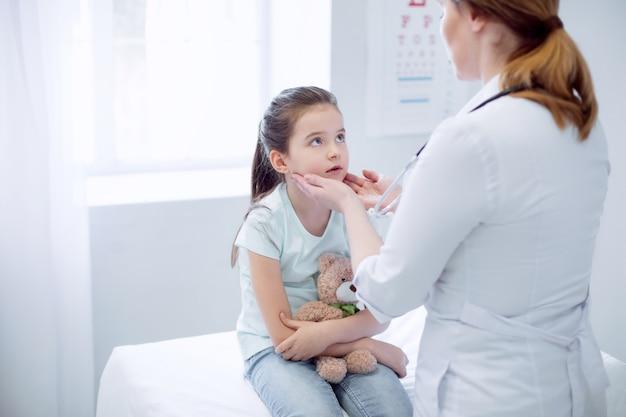 Tonsille gonfie. giovane ragazza pensierosa che si siede mentre esamina il medico femminile che prova le sue tonsille