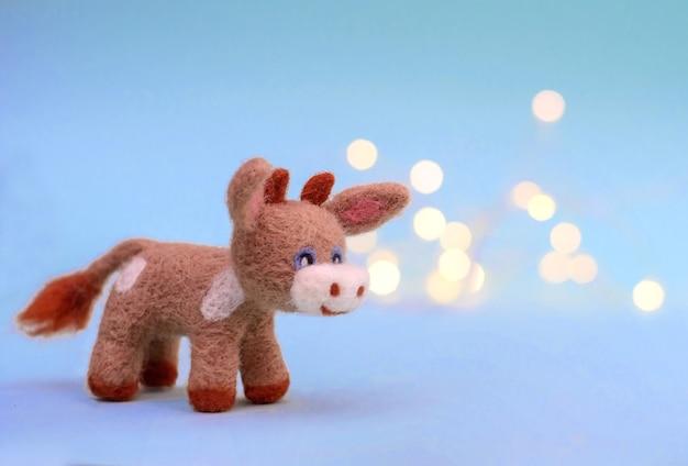 Simbolo del 2021, un giocattolo in feltro di toro o mucca su uno sfondo azzurro festivo con bokeh, con uno spazio di copia