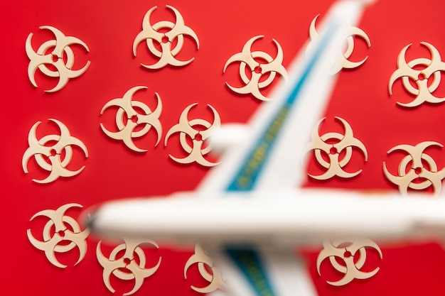 Simbolo di avviso di rischio biologico su sfondo rosso con aereo. virus epidemico del coronavirus. rifiuti biologici, radioattivi, tossici.