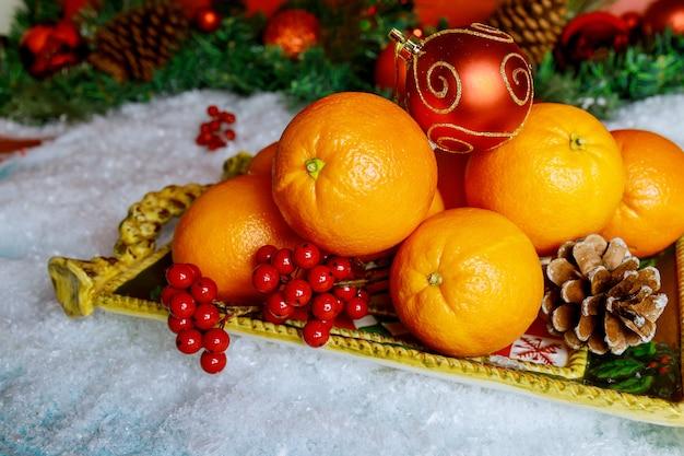 Simbolo di frutta arancione di natale o capodanno con ornamento.