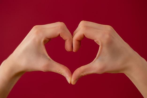 Simbolo dell'amore fatto da due mani su sfondo rosso.